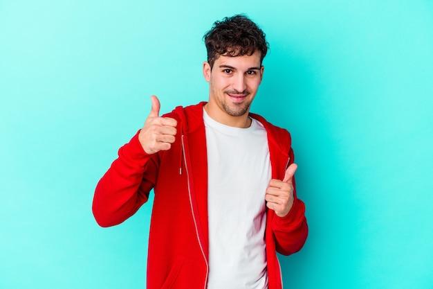 Giovane uomo isolato sulla parete blu alzando entrambi i pollici in su, sorridente e fiducioso