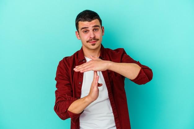 Giovane uomo isolato sulla parete blu che mostra un gesto di timeout