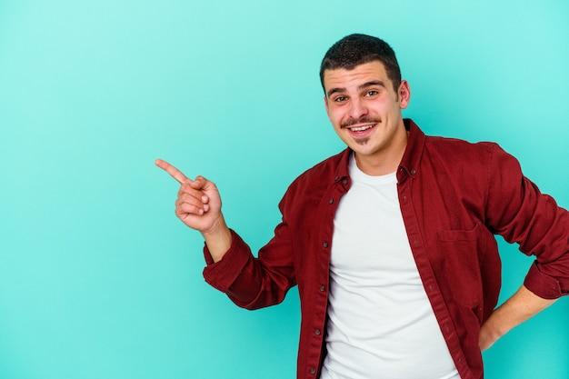 Giovane uomo isolato sulla parete blu sorridendo allegramente indicando con l'indice lontano