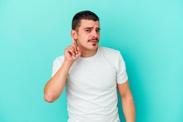 Giovane uomo isolato sulla parete blu, cercando di ascoltare un pettegolezzo