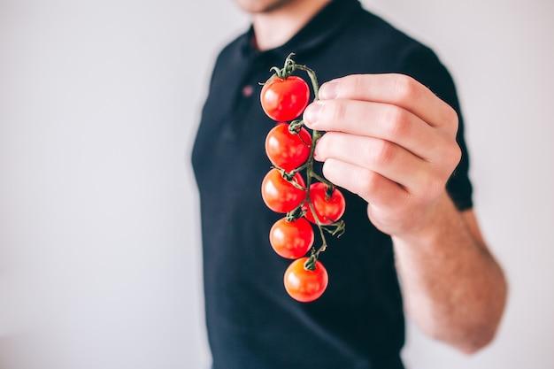 Giovane uomo isolato tagli il punto di vista del tipo che tiene i pomodori ciliegia in mani. verdura matura per cucinare.