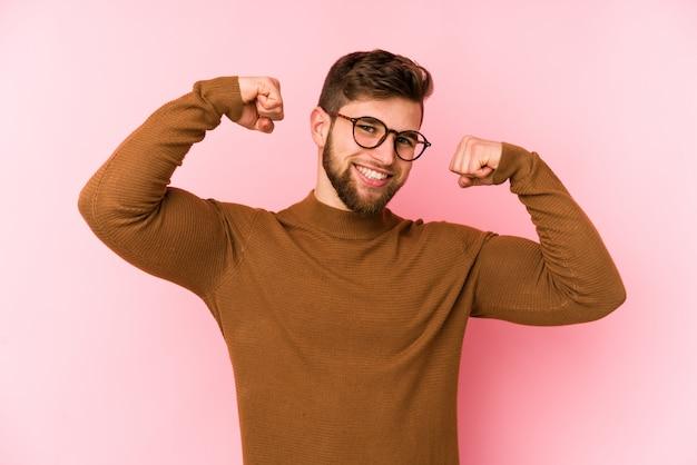 Giovane uomo isolato sul muro rosa che mostra il gesto della forza con le braccia, simbolo del potere femminile