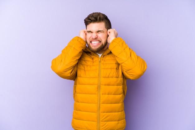 Giovane uomo isolato su sfondo viola che copre le orecchie con le mani.