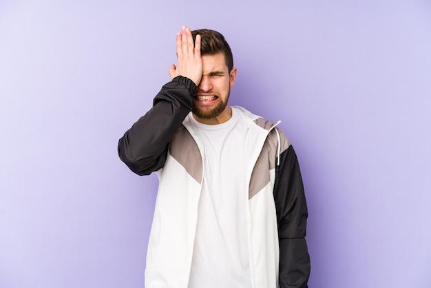 Giovane uomo isolato su sfondo viola dimenticando qualcosa, schiaffi sulla fronte con il palmo e chiudendo gli occhi.
