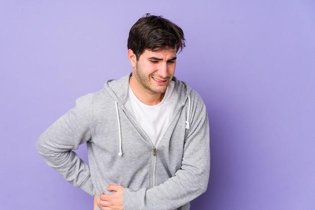 Giovane uomo isolato su sfondo viola che ha un dolore al fegato, mal di stomaco.