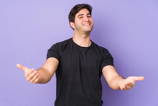 Giovane uomo isolato su sfondo viola che mostra un'espressione di benvenuto.