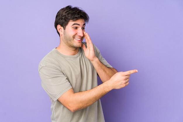 Giovane uomo isolato su uno spazio viola dicendo un pettegolezzo, indicando il lato che segnala qualcosa.