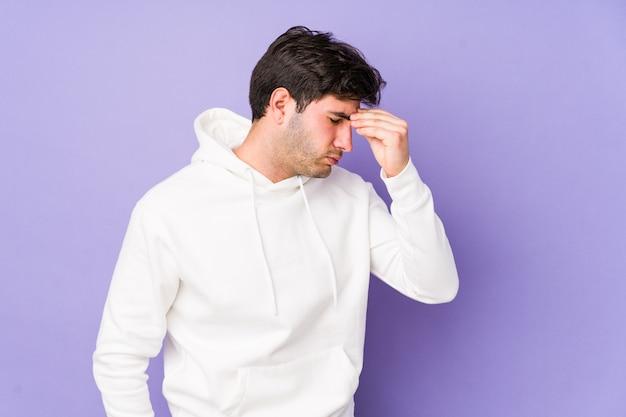 Giovane uomo isolato sulla parete viola con mal di testa, toccando la parte anteriore del viso.