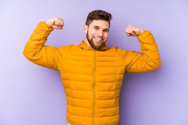Giovane uomo isolato sul muro viola che mostra il gesto della forza con le braccia, simbolo del potere femminile