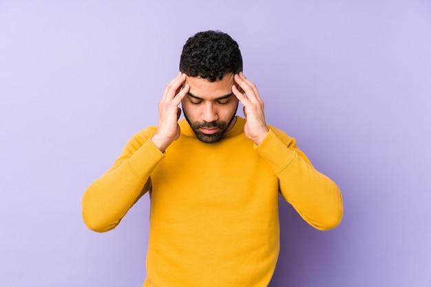 Giovane uomo isolato toccando le tempie e avendo mal di testa