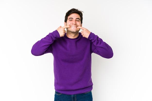 Giovane uomo isolato su uno spazio bianco sorride, puntando le dita alla bocca.