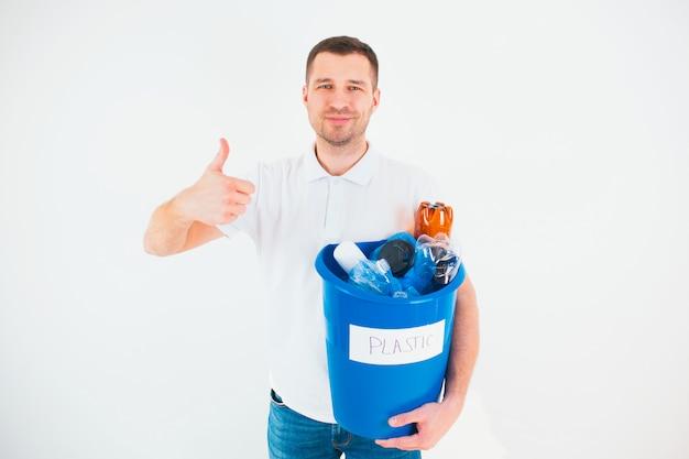 Giovane uomo isolato su un muro bianco. il ragazzo caucasico tiene il grande pollice in su e sorride. secchio blu con bottiglie di plastica all'interno. buono per il processo di riciclaggio. nessun spreco di stile di vita e ambiente.