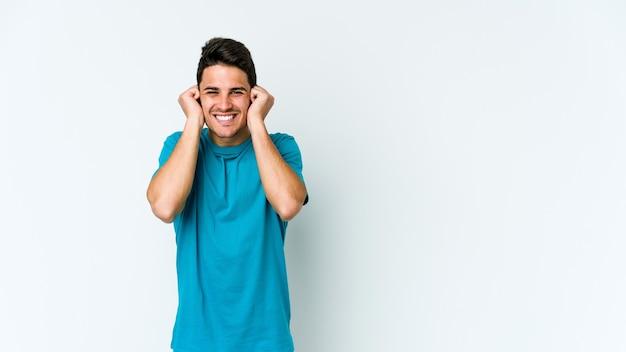 Giovane uomo isolato sul muro bianco che copre le orecchie con le mani