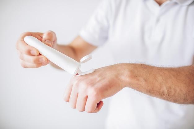 Giovane uomo isolato su un muro bianco. tagliare la vista delle mani del maschio idratante. usando la crema per la cura delle mani. procedure e trattamenti di bellezza.