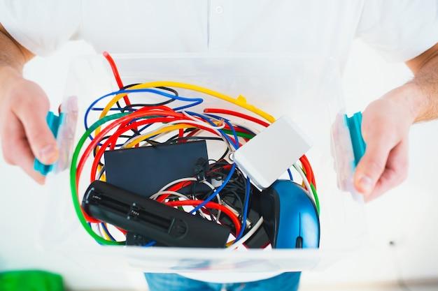 Giovane uomo isolato su un muro bianco. tagli la vista delle mani dell'uomo che tengono la scatola di plastica con i cavi e le batterie. processo di riciclaggio e stile di vita senza sprechi.