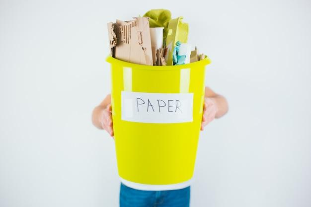 Giovane uomo isolato su un muro bianco. ragazzo tenere secchio di plastica gialla con carta in esso per il processo di riciclaggio. salute ambientale ed ecosistemica.