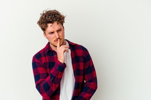 Giovane uomo isolato sul muro bianco mantenendo un segreto o chiedendo il silenzio