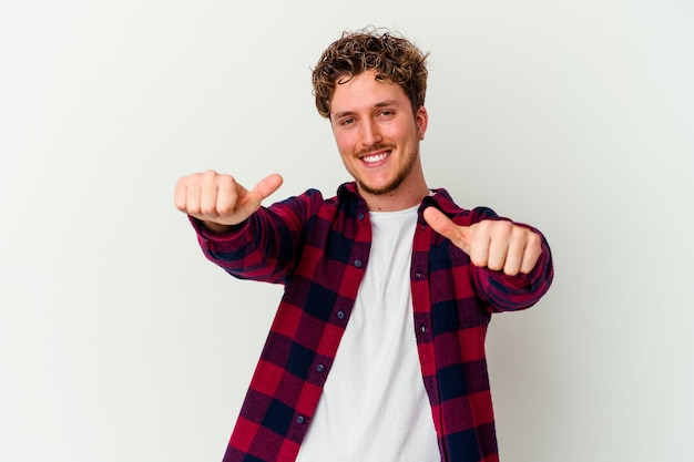 Giovane uomo isolato sul muro bianco alzando entrambi i pollici in su, sorridente e fiducioso