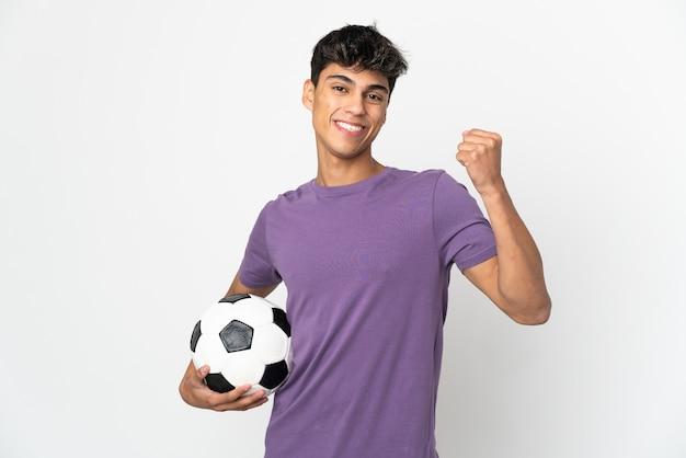 Giovane uomo sopra bianco isolato con pallone da calcio che celebra una vittoria