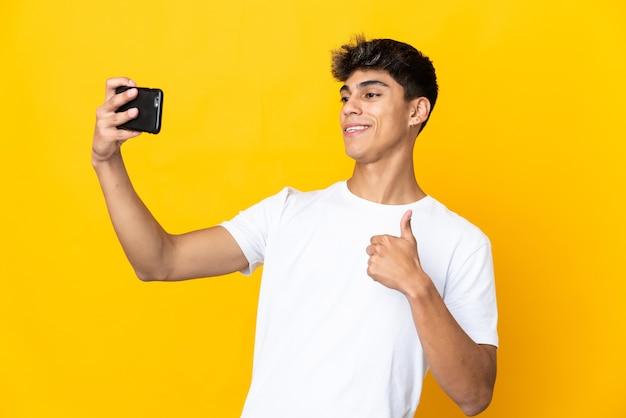 Giovane uomo su giallo isolato facendo un selfie con il telefono cellulare