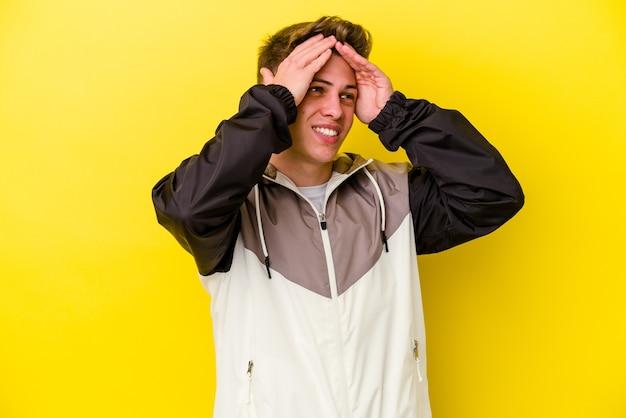 Il giovane isolato sul muro giallo ride con gioia tenendo le mani sulla testa. concetto di felicità