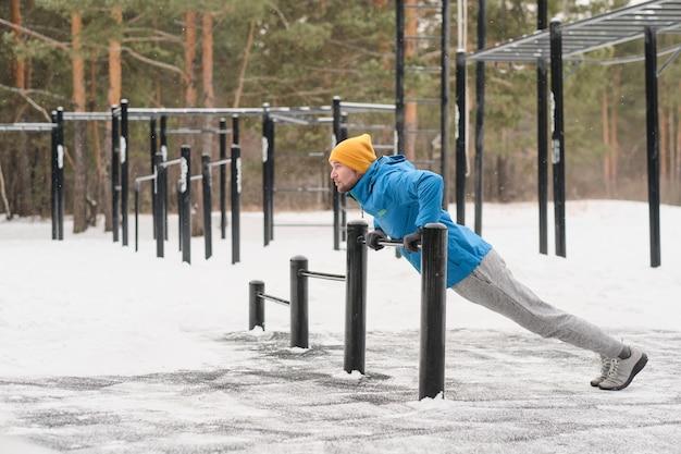 Giovane uomo in giacca utilizzando la barra orizzontale bassa per praticare pull-up sul campo sportivo in inverno