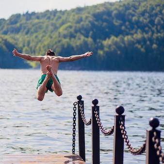 Il giovane che salta nell'acqua