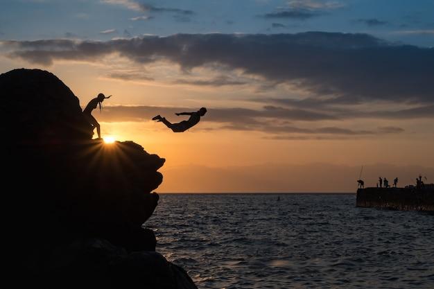 Giovane uomo che salta giù dalla scogliera nell'oceano sullo sfondo del tramonto. idea di concetto di affari