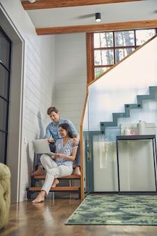 Giovane uomo e donna seduti sulle scale in una casa moderna di lusso e guardando lo schermo del computer