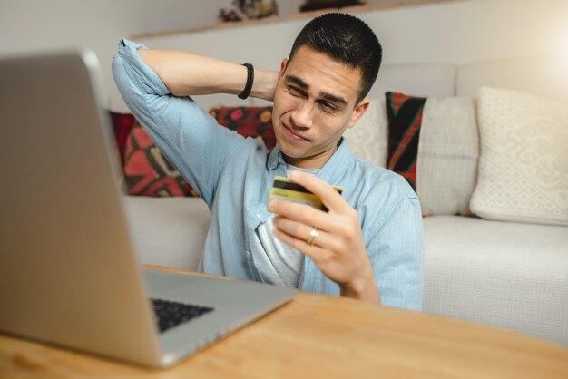 Giovane uomo al computer portatile a casa tenendo la carta di credito.