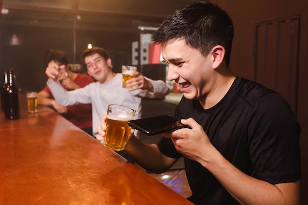 Un giovane che ride mentre trasmette una voce audio insieme ai suoi amici ubriachi al bar.