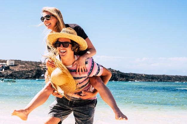 Giovane che ride con la ragazza sulle spalle?
