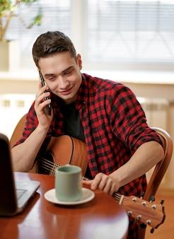 Un giovane impara a suonare la chitarra usando internet, laptop, lezione online