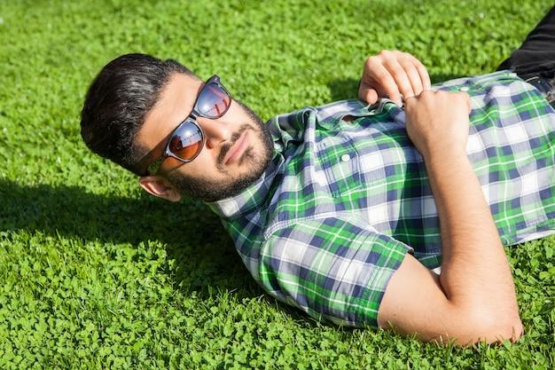 Il giovane si sdraia sul prato e si gode l'estate.