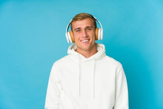 Il giovane che ascolta la musica isolata sulla parete blu si sente orgoglioso e sicuro di sé, esempio da seguire