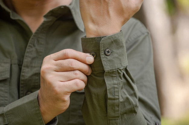 Giovane uomo in camicia a maniche lunghe verde in piedi nel parco