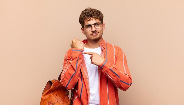 Il giovane che sembra impaziente e arrabbiato, indica l'orologio, chiede puntualità, vuole essere puntuale. concetto di studente