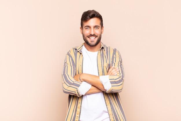 Giovane che sembra un uomo d'azione felice, orgoglioso e soddisfatto che sorride con le braccia incrociate