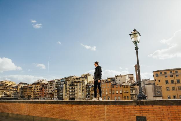 Giovane uomo che guarda la città vecchia di firenze, toscana, italia.