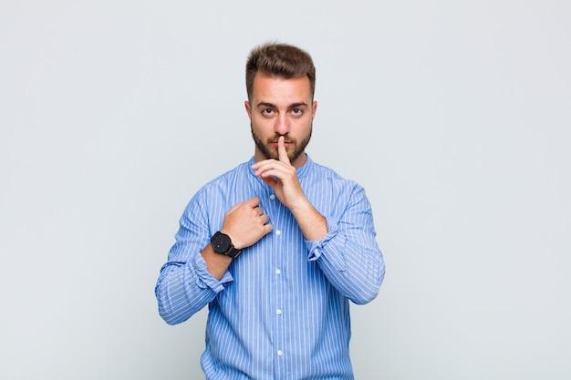 Giovane che sembra serio e croce con il dito premuto sulle labbra che chiedono silenzio o silenzio, mantenendo un segreto