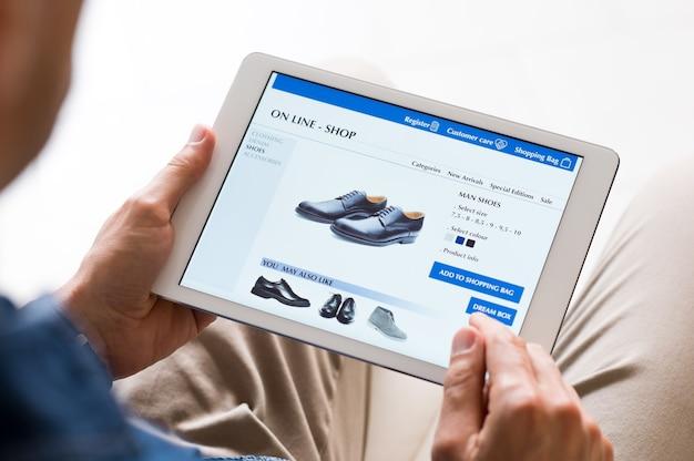 Giovane uomo che guarda le scarpe online