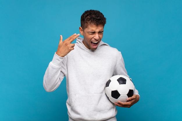 Giovane che sembra infelice e stressato, gesto di suicidio che fa il segno della pistola con la mano, indicando la testa. concetto di calcio