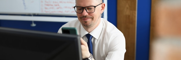 Il giovane esamina lo smartphone e il monitor del computer sul posto di lavoro