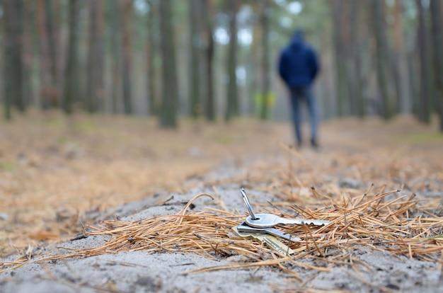 Il giovane perde il suo mazzo di chiavi sul percorso russo di legno dell'abete di autunno. disattenzione e concetto di perdere le chiavi