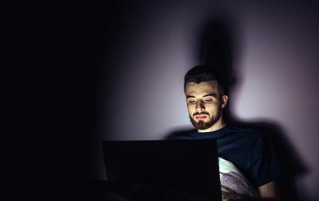 Giovane uomo sdraiato sul letto e guarda lo schermo del laptop. ragazzo calmo e concentrato che fa gli straordinari giocando o divertendosi. stanza di notte.