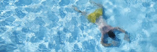 Giovane che si trova sul fondo della vista dall'alto della piscina. concetto di aiuto all'annegamento