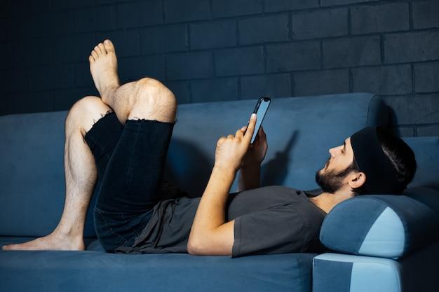 Giovane uomo sdraiato sul divano e utilizza lo smartphone sullo sfondo del muro di mattoni.