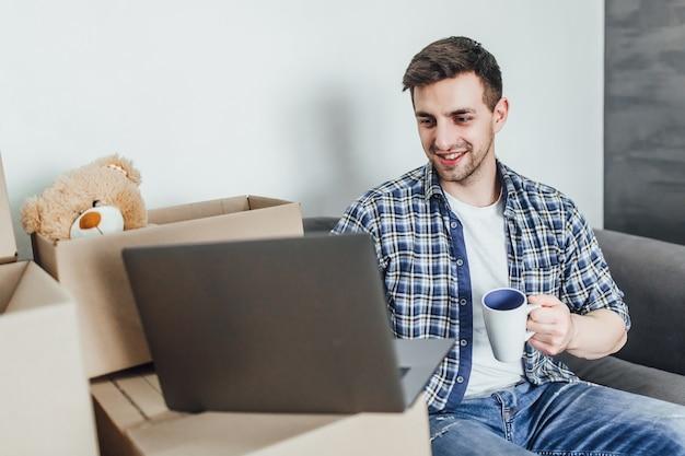 Giovane uomo sdraiato sul divano con scatole da imballaggio vicino e pianificando sul laptop le cose successive di cui ha bisogno