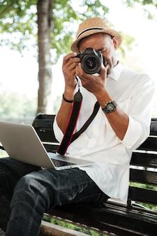 Il giovane fa la foto nel parco con la macchina fotografica