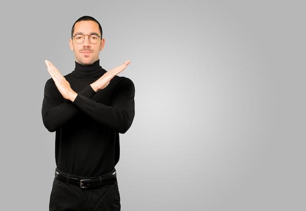 Giovane che fa un gesto di non attraversare con le braccia